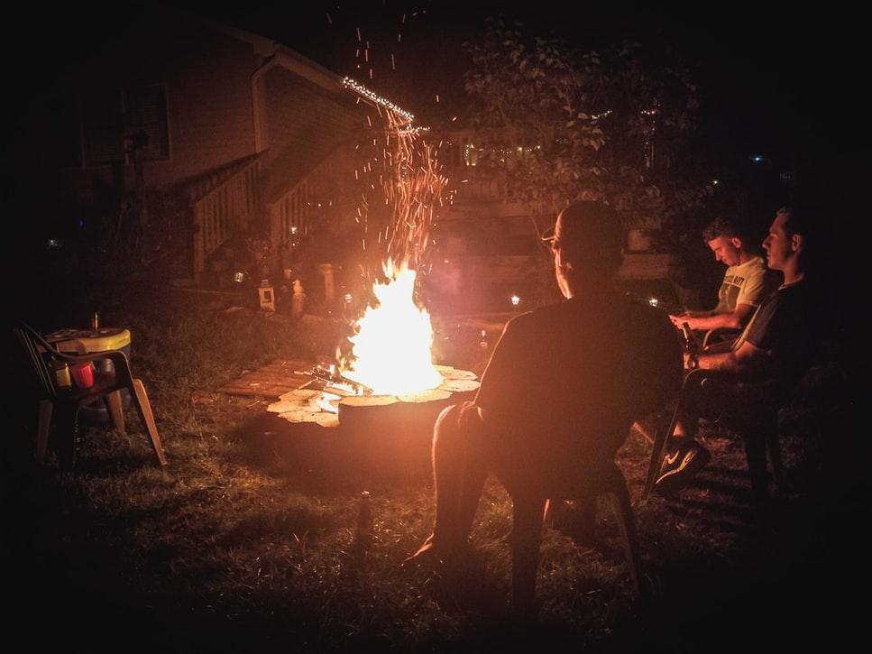 people sitting around patio garden campfire at night
