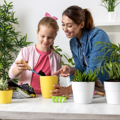 woman and girl planting plants in pots